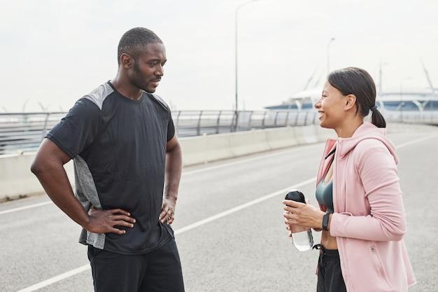 街に立って一緒にトレーニングについて話し合うスポーツウェアの若いカップル