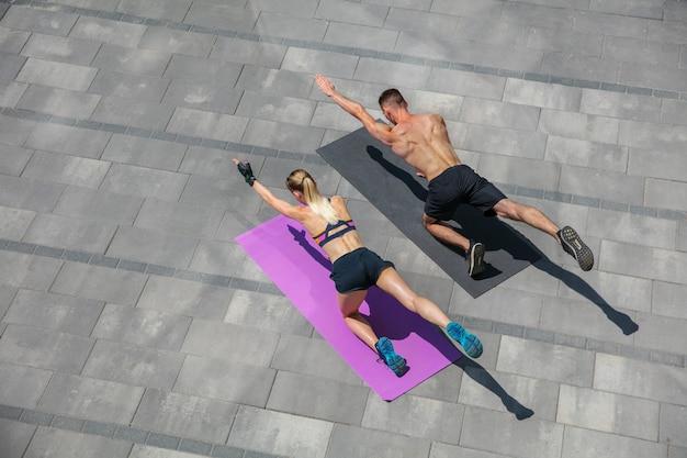야외에서 아침 운동을 하는 스포츠 복장을 한 젊은 부부, 건강한 생활 방식