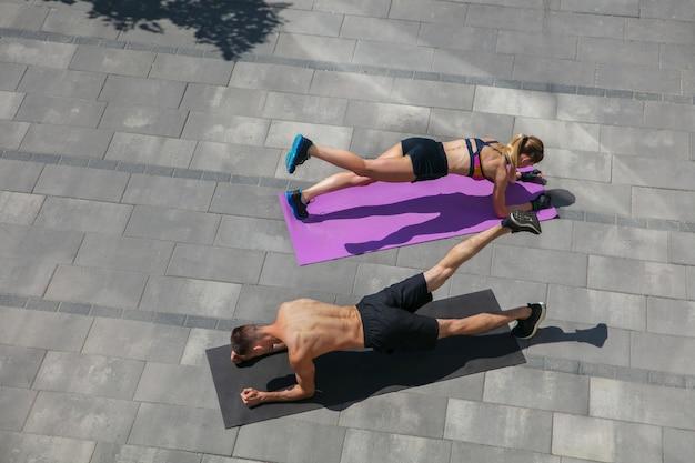 屋外で朝のトレーニングをしているスポーツ服の若いカップル、健康的なライフスタイル