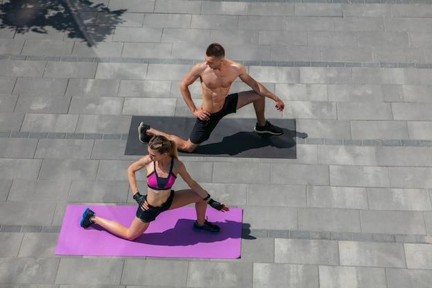 야외에서 건강한 생활 방식으로 아침 운동을 하는 스포츠 복장을 한 젊은 부부