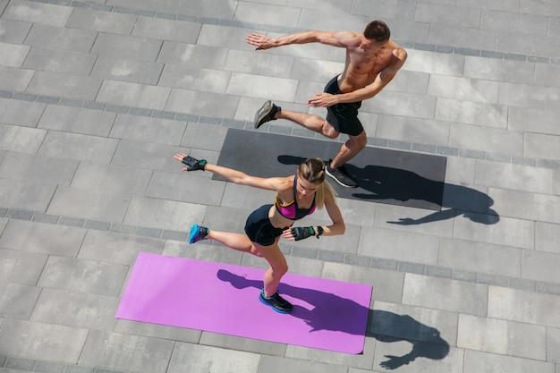 屋外の朝のトレーニングを行うスポーツ服装の若いカップル。
