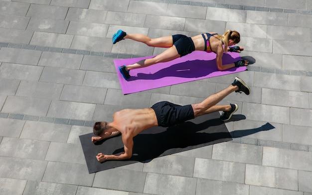 Молодая пара в спортивной одежде делает утреннюю тренировку на открытом воздухе.