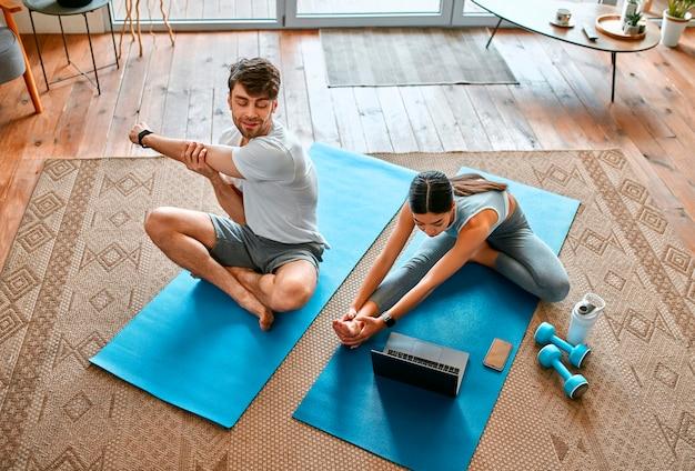 ラップトップからのビデオチュートリアルを使用して自宅のリビングルームでエクササイズをしているスポーツウェアの若いカップル。健康的なライフスタイル、スポーツ、ヨガ、フィットネス。
