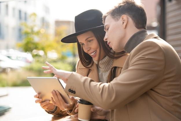 세련된 캐주얼웨어를 입은 젊은 부부는 야외 카페에서 휴식을 취하고 태블릿 디스플레이를 가리키는 남자 동안 온라인 정보에 대해 토론합니다.