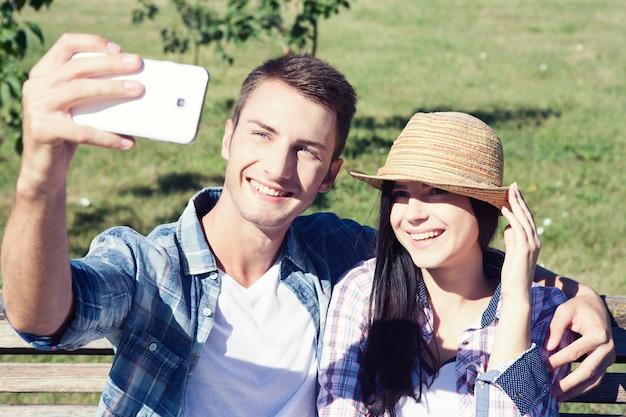 공원에서 산책에 여름 옷에 젊은 부부는 셀카를 만든다