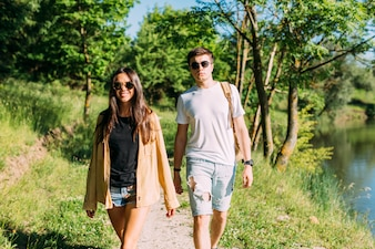Young couple in sunglasses walking near lake