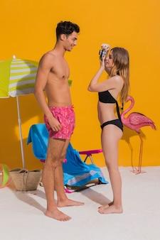Молодая пара в купальных костюмах фотографирует