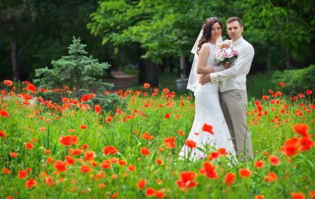 公園の赤いポピーのエリアで若いカップル。結婚式の日の新婚夫婦