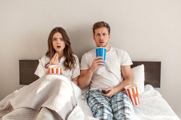 ベッドで若いカップル。驚いた美しい男性と女性は、ポップコーンを食べて、寝室で一緒にテレビを見ています