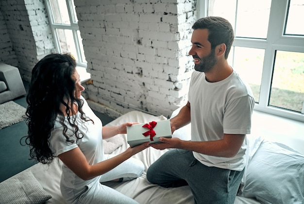 ベッドの中で若いカップル。魅力的な男は彼の幸せなガールフレンド、関係のロマンスに贈り物を与えています