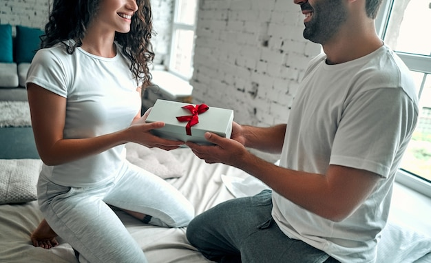 침대에서 젊은 부부. 매력적인 남자가 행복한 여자 친구에게 선물을주고, 관계의 로맨스