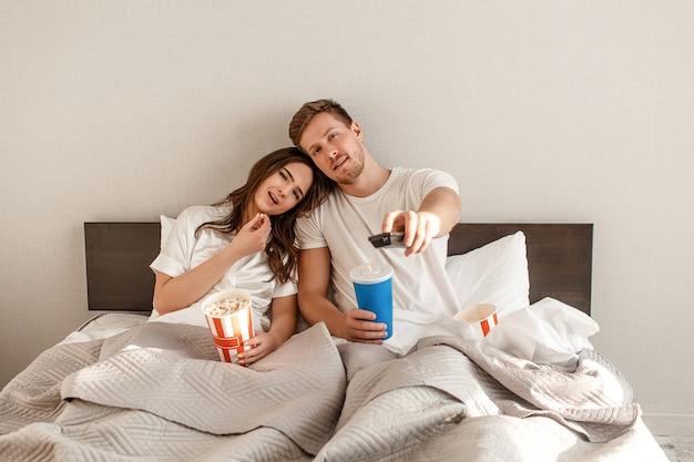 ベッドで若いカップル。笑顔の美しい男性と女性は、リモコンを押しながらテレビを見ながらポップコーンを食べています