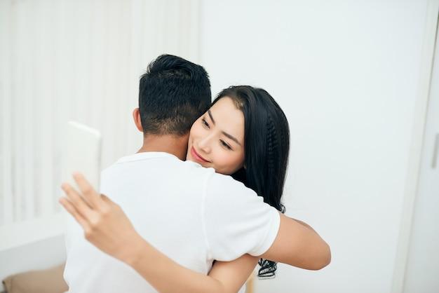 침실에서 젊은 부부. 매력적인 여성이 아침에 들어오는 메시지를 확인하고 있다