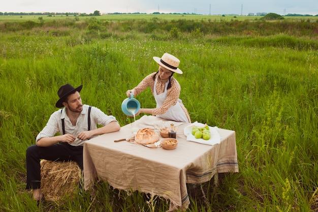 Молодая пара в поле, ест и пьет