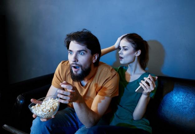 彼らの新しいアパートで映画を見ている若いカップル