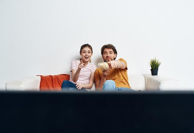 Молодая пара в своей новой квартире смотрит телевизор