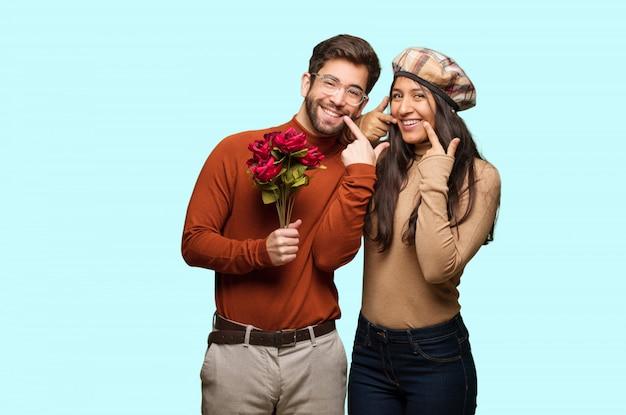 Молодая пара в день святого валентина улыбается, указывая рот