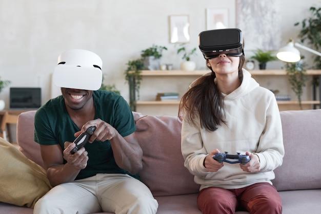 ソファに座って、部屋のチームでビデオゲームをプレイするバーチャルリアリティメガネの若いカップル