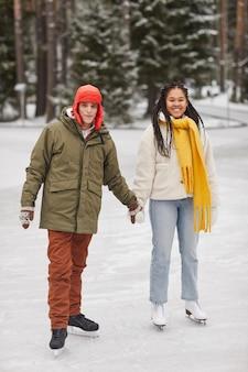 スケートリンクで一緒にスケートを手をつないで暖かい服を着た若いカップル