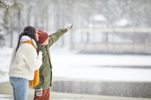 雪が降っているときに屋外に立っている何かを見ている暖かい服を着た若いカップル