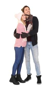 白い表面に暖かい服を着た若いカップル。冬休みの準備ができました