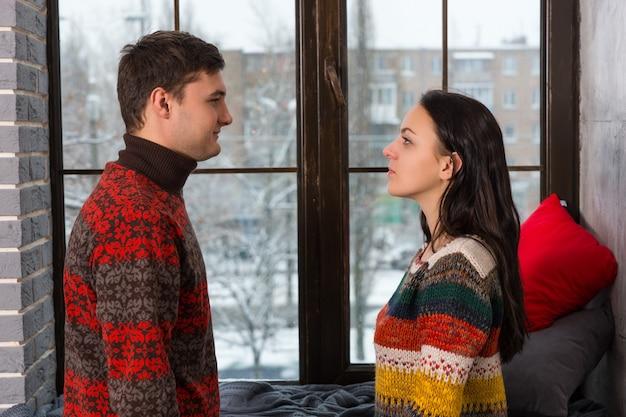 枕と毛布で窓辺の近くに立っている間お互いを見ている暖かいニットセーターの若いカップル