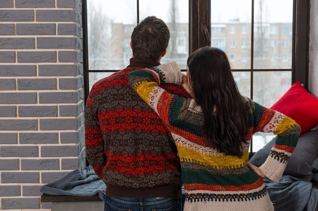 枕と毛布で窓辺の近くに立っている間、窓の外を見ている暖かいニットセーターの若いカップル