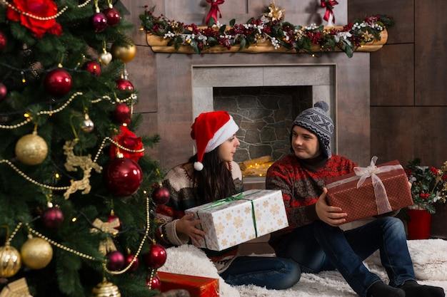 따뜻한 스웨터와 재미있는 겨울 모자를 쓴 젊은 부부는 크리스마스 트리 앞의 깔개에 앉아 있는 동안 선물을 기뻐합니다