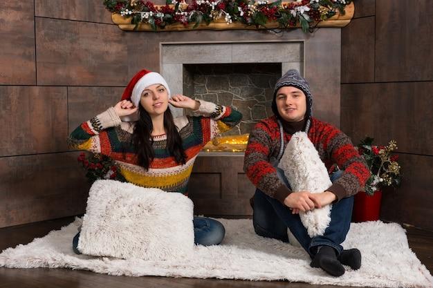 따뜻한 스웨터와 재미있는 겨울 모자를 쓴 젊은 부부는 장식된 벽난로 앞 깔개에 앉아 있다