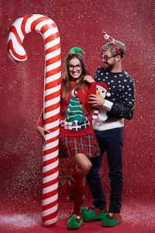 奇妙なクリスマスの服を着た若いカップル