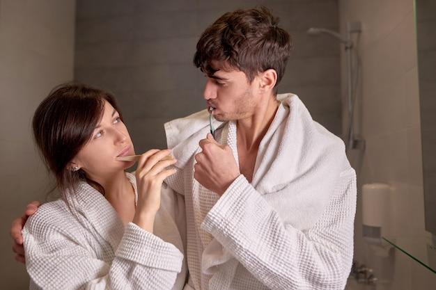 Молодая пара в белых халатах вместе чистит зубы в ванной комнате