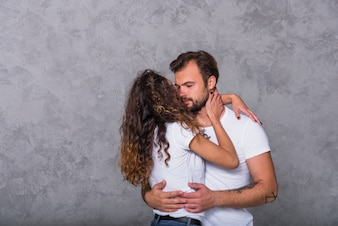 Young couple in white hugging