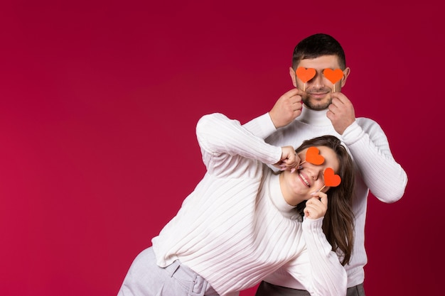 Молодая пара в белых свитерах держит красные сердца ручной работы, закрывая глаза. красный фон