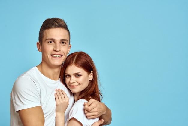 青い壁にポーズをとって白いtシャツの若いカップル
