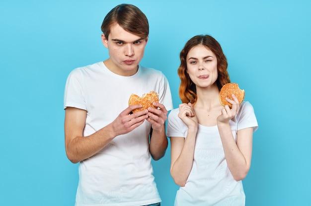 手にハンバーガーファーストフードスナックと白いtシャツを着た若いカップル。高品質の写真