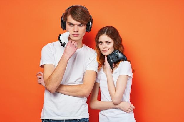 エンターテインメントを再生する手にジョイスティックと白いtシャツを着た若いカップル。高品質の写真