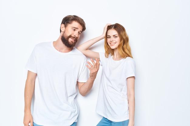 흰색 티셔츠 통신 옷 청바지 밝은 배경에 젊은 부부