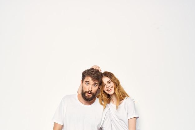 白いtシャツの若いカップルは一緒に友情を抱きしめます