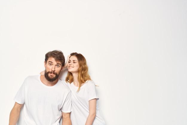 흰색 티셔츠를 입은 젊은 부부는 우정을 함께 껴안습니다.