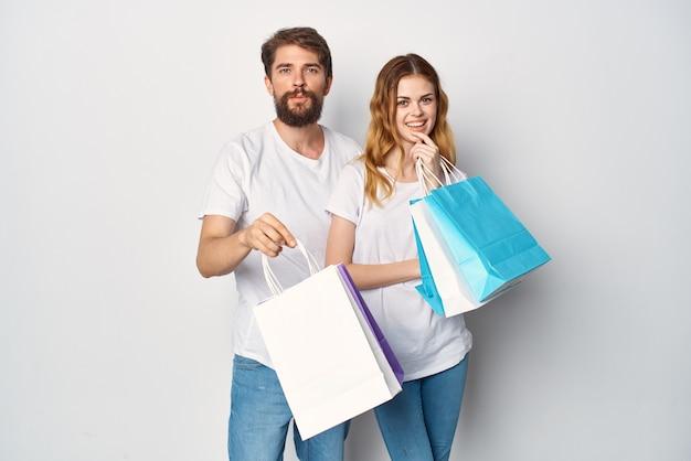 Молодая пара в белых футболках, делая покупки весело