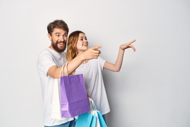 手でバッグとショッピングの楽しみと白いtシャツの若いカップル