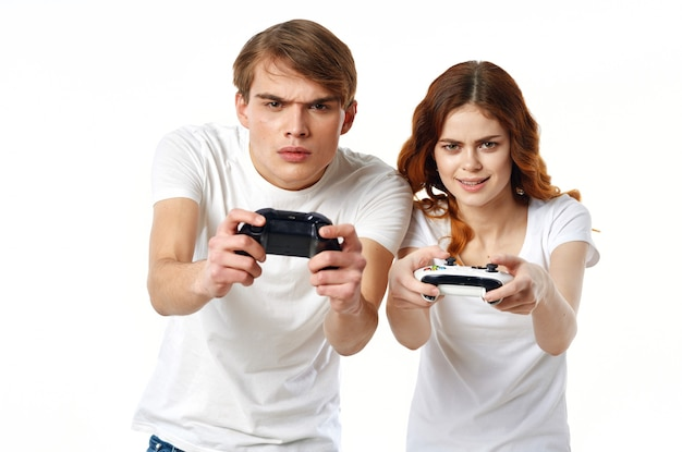 手にジョイスティックを持った白いtシャツを着た若いカップルビデオゲームエンターテインメント