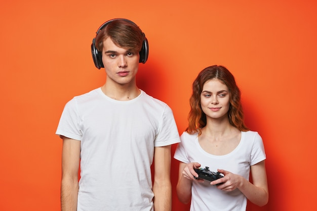 コンソールオレンジ色の背景を再生ジョイスティックと白いtシャツの若いカップル