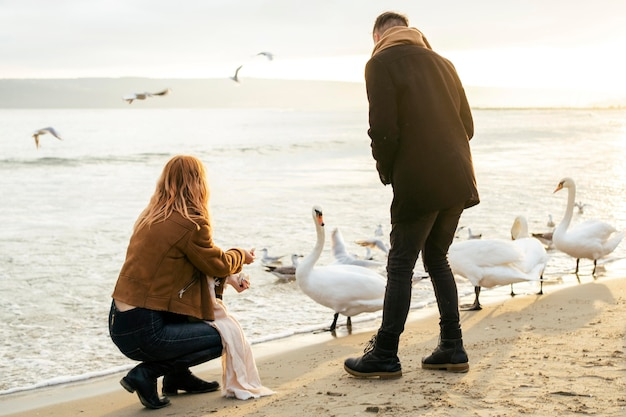 Молодая пара зимой на пляже с птицами
