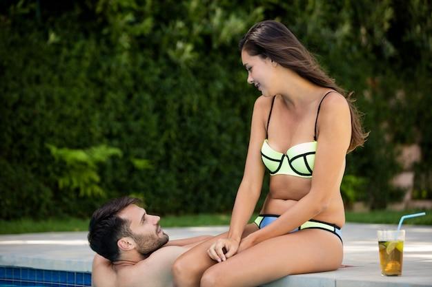 화창한 날에 수영장에서 서로 상호 작용하는 젊은 부부