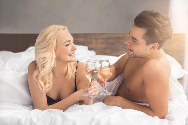 幸せなベッドで若いカップルの親密な関係