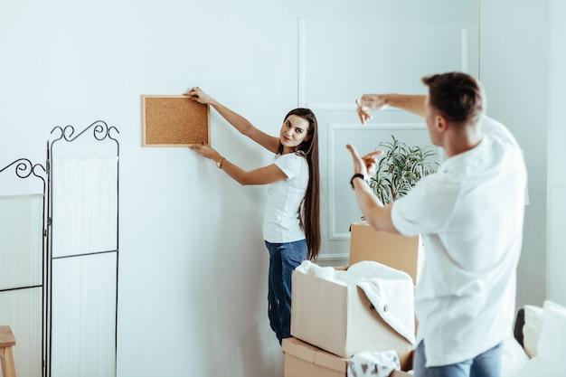 그들의 새 아파트의 인테리어를 발명하는 젊은 부부