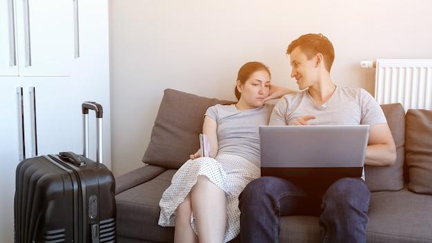 Молодая пара заказывает трансфер в аэропорт на ноутбуке, сидя на диване у себя дома. в отпуск едут с паспортами и чемоданом. выбор и бронирование тура и отеля.