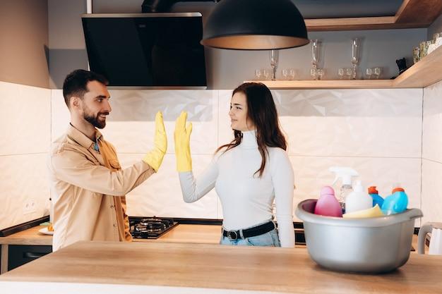 若いカップルが台所で掃除した後、ハイタッチをしている