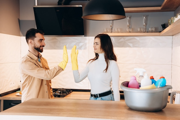 Young couple is giving high five after cleaning in kitchen